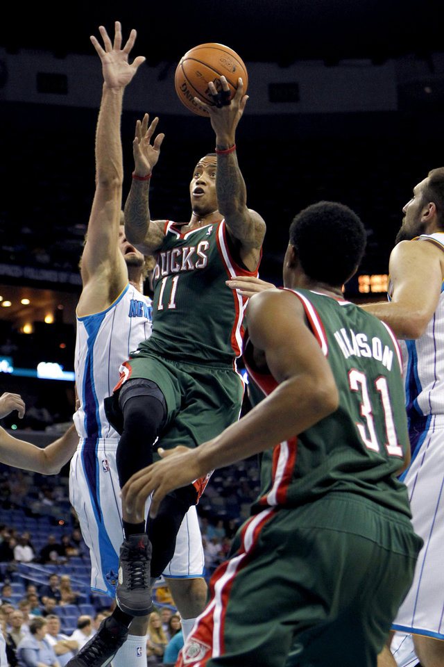 Milwaukee Bucks guard Monta Ellis (11) drives to the basket between New Orleans Hornets center Robin Lopez, left, and forward Ryan Anderson, right, in the first half of an NBA basketball game in New Orleans, Monday, Dec. 3, 2012. (AP Photo/Gerald Herbert)