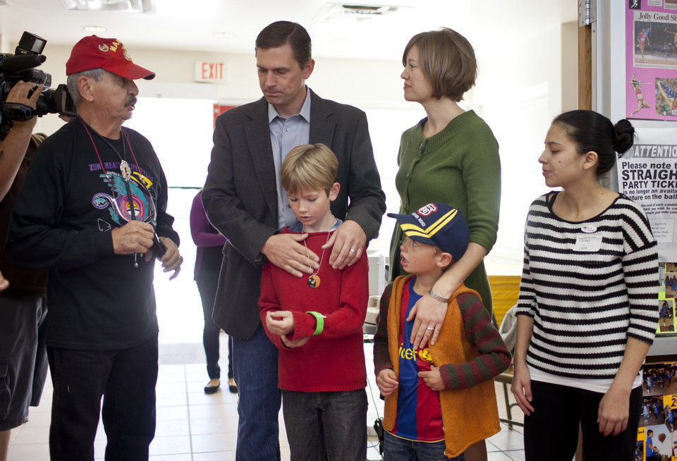 Photo -   New Mexico Democratic U.S. Senate candidate, Rep. Martin Heinrich, speaks with voter David C De Baca, left, while waiting with his family, Carter, 9, his wife, Julie, and Micah, 6. Poll worker Ashley Chavez, right, wait to tell them when to advance in line. The family went to vote Tuesday, Nov. 6, 2012, at Bandelier Elementary School in Albuquerque, NM. (AP Photo/Craig Fritz)