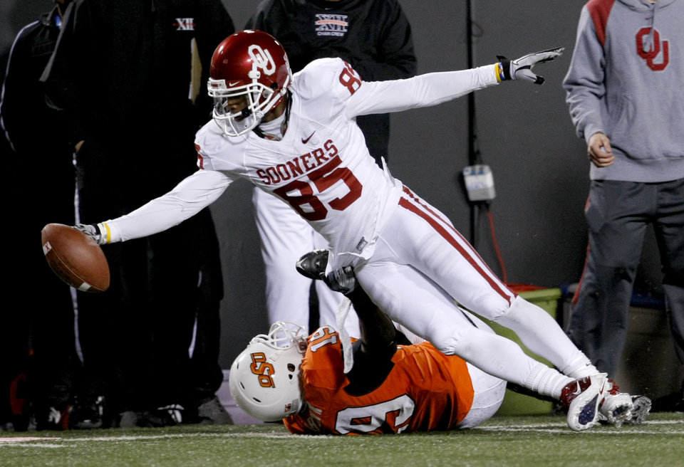 Photo - Oklahoma's Ryan Broyles (85) dives over Oklahoma State's Brodrick Brown (19) during the Bedlam college football game between the University of Oklahoma Sooners (OU) and the Oklahoma State University Cowboys (OSU) at Boone Pickens Stadium in Stillwater, Okla., Saturday, Nov. 27, 2010. Photo by Bryan Terry, The Oklahoman