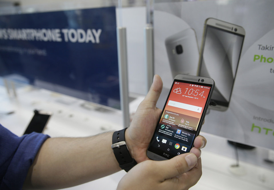Photo - A salesperson demonstrates the new HTC One M9 smartphone that went on sale Friday, April 10, 2015, at a Best Buy store in San Francisco. HTC improved its camera and has added home-screen personalization based on location. Prices vary by carrier. No-contract versions generally start at about $650. (AP Photo/Eric Risberg)