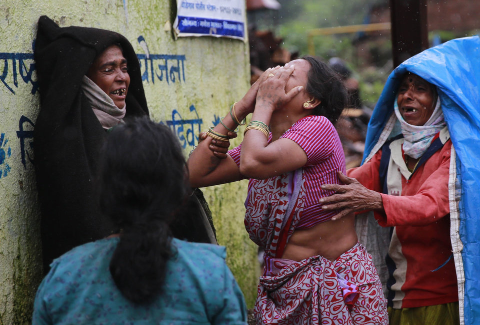 Photo - AP10ThingsToSee - Relatives wail after seeing the body of a victim of massive landslide in the Malin village in Pune district of western Maharashtra state, India, Thursday, July 31, 2014. (AP Photo/Rafiq Maqbool)