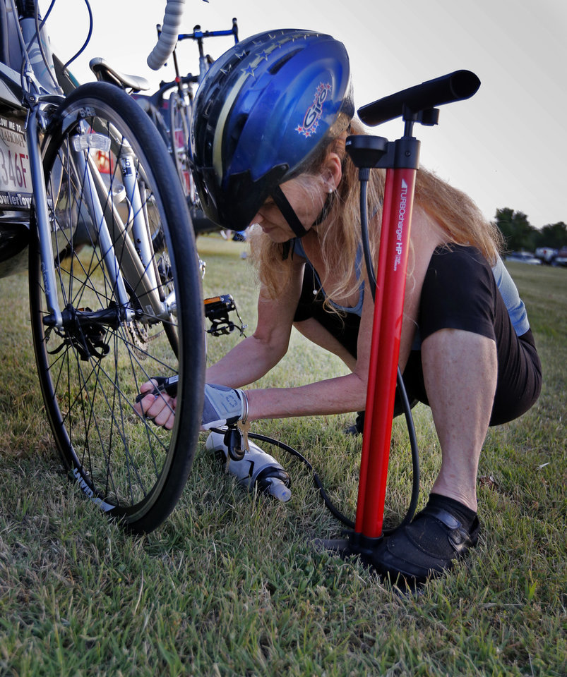 Photo -  Madeline Bradstock airs her tires as she prepares to ride in the Norman Conquest bike ride. PHOTO BY STEVE SISNEY, THE OKLAHOMAN   STEVE SISNEY