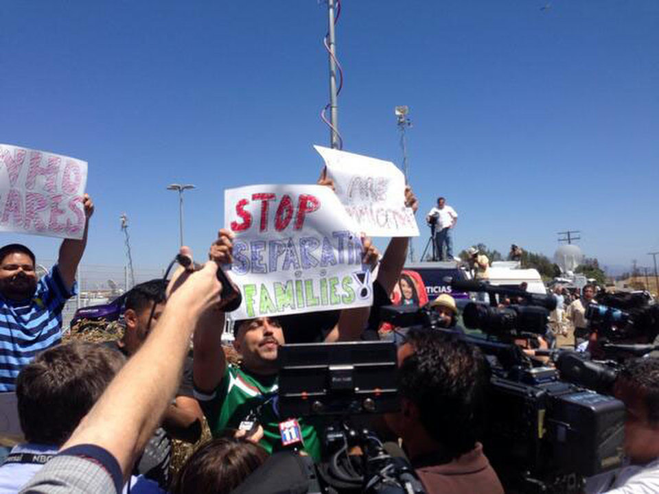 Photo - Counter-protestors hold pro-immigrant banners as protestors stand in the road blocking a bus carrying 140 immigrants on the way to be processed at the Murrieta border patrol station on Tuesday, July 1, 2014. The migrants are bused to a border patrol facility in Murrieta, about an hour north of San Diego, for processing. Federal immigration authorities there will determine whether they will be held or released pending deportation proceedings.(AP Photo/The Press-Enterprise, Sarah Burge)