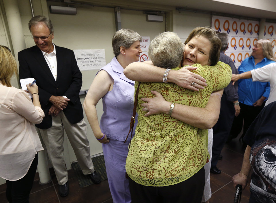 Photo - Mary Bishop (right) hugs a supporter as her partner Sharon Baldwin (center) and attorney Don Holladay (left) stand near after a press conference at the Dennis R. Neill Equality Center in Tulsa, Okla. on Monday, October 6, 2014. Bishop and Baldwin were the first same-sex couple in Oklahoma to receive a marriage license. MATT BARNARD/Tulsa World