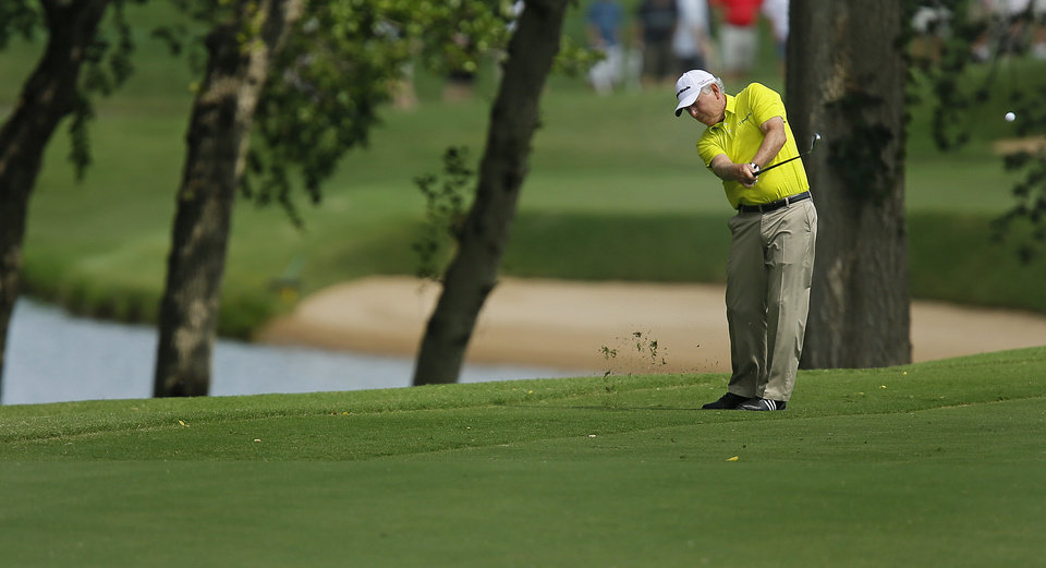 Photo - Hale Irwin hits an approach shot on the ninth hole during the first round of the U.S. Senior Open Championship golf tournament at Oak Tree National in Edmond, Okla. on Thursday, July 10, 2014. Photo by Chris Landsberger, The Oklahoman