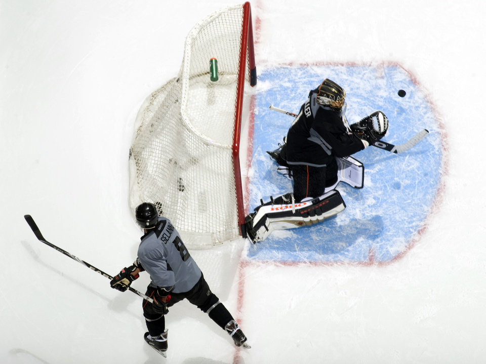 Anaheim Ducks\' Teemu Selanne, bottom left, watches as goalie Jonas Hiller goes for the puck during opening day of NHL hockey training camp, Sunday, Jan. 13, 2013, in Anaheim, Calif. (AP Photo/The Orange County Register, Michael Goulding) MAGS OUT; LOS ANGELES TIMES OUT; MANDATORY CREDIT