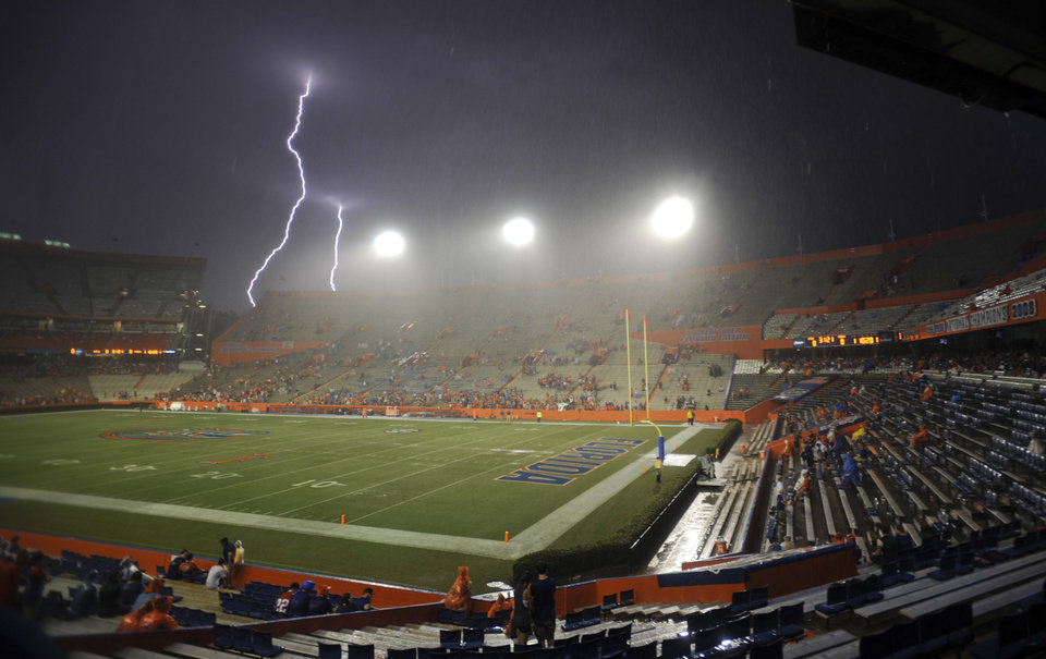 Photo - Lightning strikes near Ben Hill Griffin Stadium at Florida Field during a weather delay before an NCAA college football game between Florida and Idaho in Gainesville, Fla., Saturday, Aug. 30, 2014. (AP Photo/Phil Sandlin)