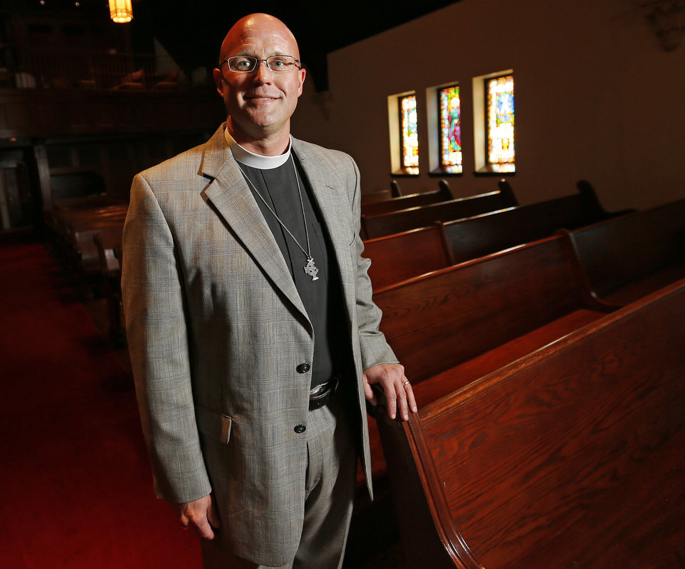 Photo - The Rev. Justin Lindstrom, the new dean at St. Paul's Episcopal Cathedral, stands in the sanctuary of the historic downtown Oklahoma City church, 127 NW 7.   NATE BILLINGS - NATE BILLINGS