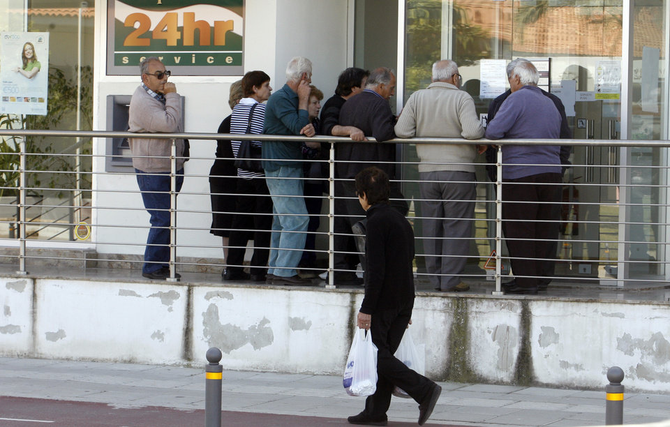 Photo - People wait outside a Coop Bank branch in Nicosia, Cyprus, Thursday, March 28, 2013. Cypriots get their first chance to access their savings in almost two weeks when the country's banks reopen Thursday - albeit with strict restrictions on transactions - after being closed due to the country's acute financial crisis. Lines were starting to form outside banks Thursday morning ahead of the official opening for six hours at noon (1000 GMT). (AP Photo/Philippos Christou)