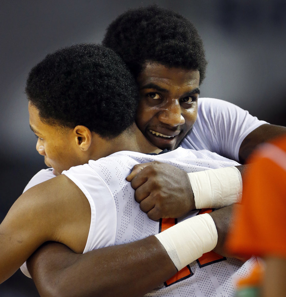 Photo - Deondre Clark, right, hugs teammate Isaih Shaputis as Douglass defeats the Stilwell Indians 78-50 in the finals of the State Class 4A Boys Basketball Tournament at the Fairgrounds Arena on Saturday, March 15, 2014, in Oklahoma City, Okla. Photo by Steve Sisney, The Oklahoman