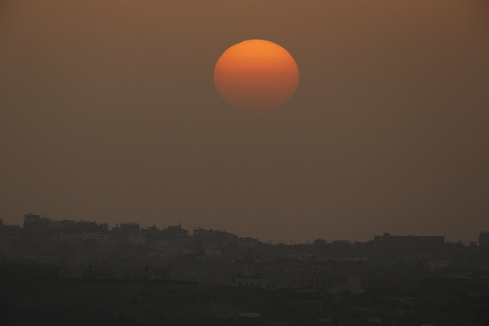Photo - The sun sets over the Gaza Strip, as seen from the Israel-Gaza border, on Friday, July 11, 2014. Gaza rocket fire by Palestinian militants struck a gas station and set it ablaze Friday in southern Israel, seriously wounding one person as rocket fire also came from Lebanon for the first time in the four-day-long offensive. Rocket fire by Palestinian militants continued from Gaza toward various locations in southern Israel. (AP Photo/Lefteris Pitarakis)