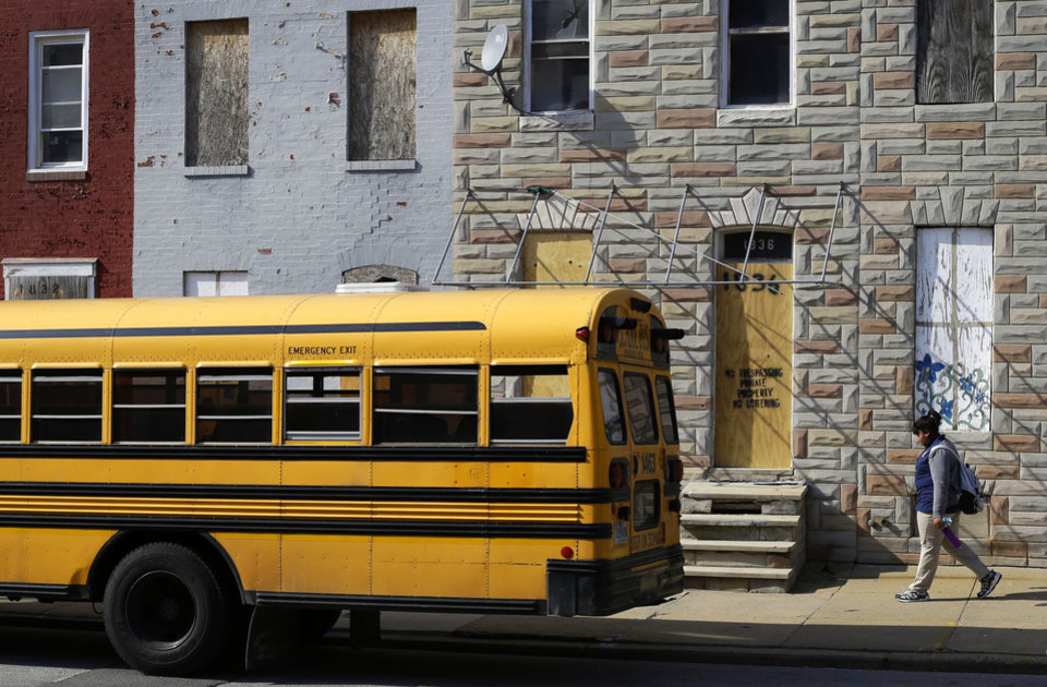 Photo - In this April 9, 2013 picture, a student walks past vacant row houses to a waiting school bus as school gets out for the day in Baltimore. The U.S. Census Bureau estimates that 20 percent of American children are impoverished. An estimated 16,000 buildings are vacant or abandoned in Baltimore. (AP Photo/Patrick Semansky)