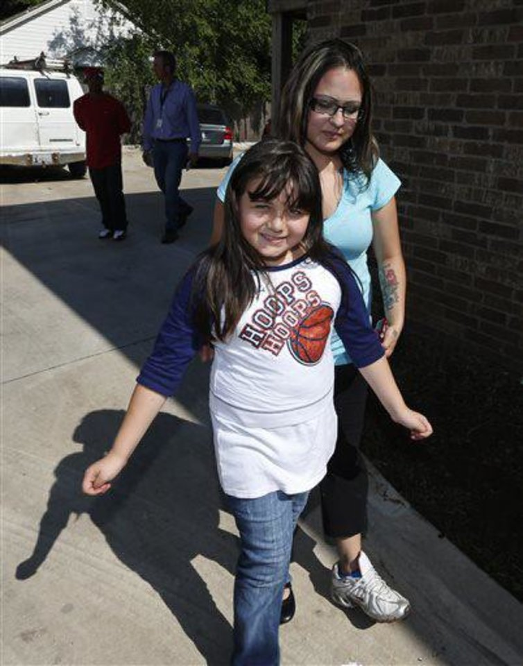 Jazmin Rodriguez, left, smiles as she walks with her mother, LaTisha Garcia, right, following an interview in Moore, Okla., Thursday, May 23, 2013. Garcia carried her injured daughter away from a school that was hit by a tornado on Sunday. (AP Photo/Sue Ogrocki)