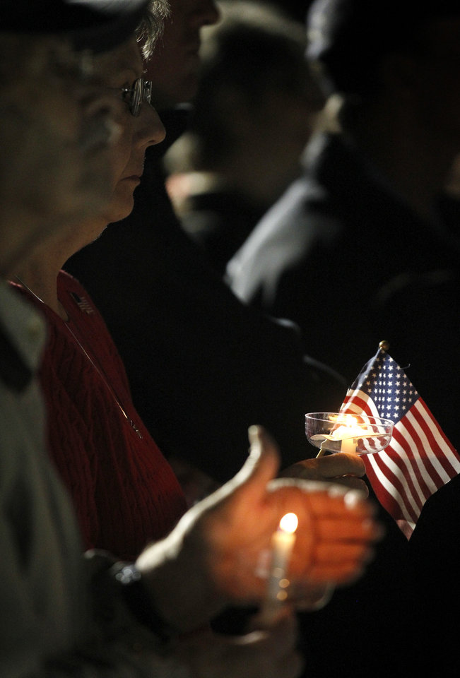 Photo -   People gather in Centennial Plaza in Midland, Texas on Saturday, Nov. 17, 2012 for a candlelight vigil held in honor of four veterans who were killed when a freight train hit a parade float Thursday. (AP Photo/Midland Reporter-Telegram, James Durbin)