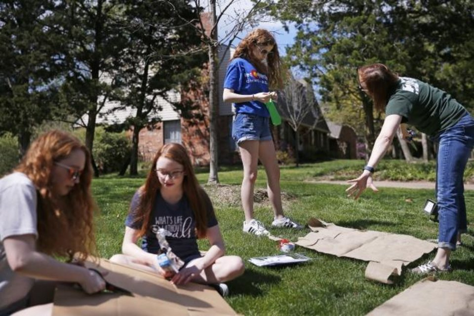 Photo -  Kirsten Cash, right, and her daughters, McKenna, 19, left, Lorelei, 14, and Tierney, 17, second from right, assemble a scene for a drive-thru Stations of the Cross outside their Edmond home. [Bryan Terry/The Oklahoman]