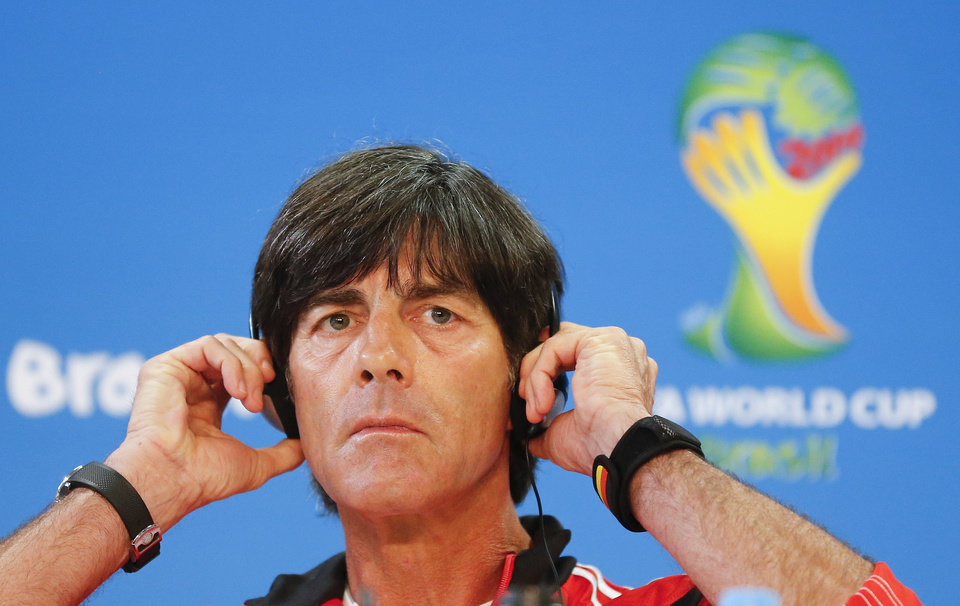 Photo - Germany's soccer team coach Joachim Loew listens with headphones during a press conference at the Estadio Beira-Rio Stadium in Porto Alegre, Brazil, Sunday, June 29, 2014. Germany will play Algeria in a World Cup round of 16 soccer match on June 30. (AP Photo/Frank Augstein)