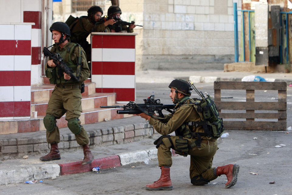 Photo - Israeli army soldiers take positions during clashes with Palestinians in an early morning operation in the West Bank city of Jenin, Wednesday, July 2, 2014. Tensions have mounted between Israel and the Palestinians after the bodies of three Israeli teens were found in the West Bank more than two weeks after they went missing. (AP Photo/Mohammed Ballas)