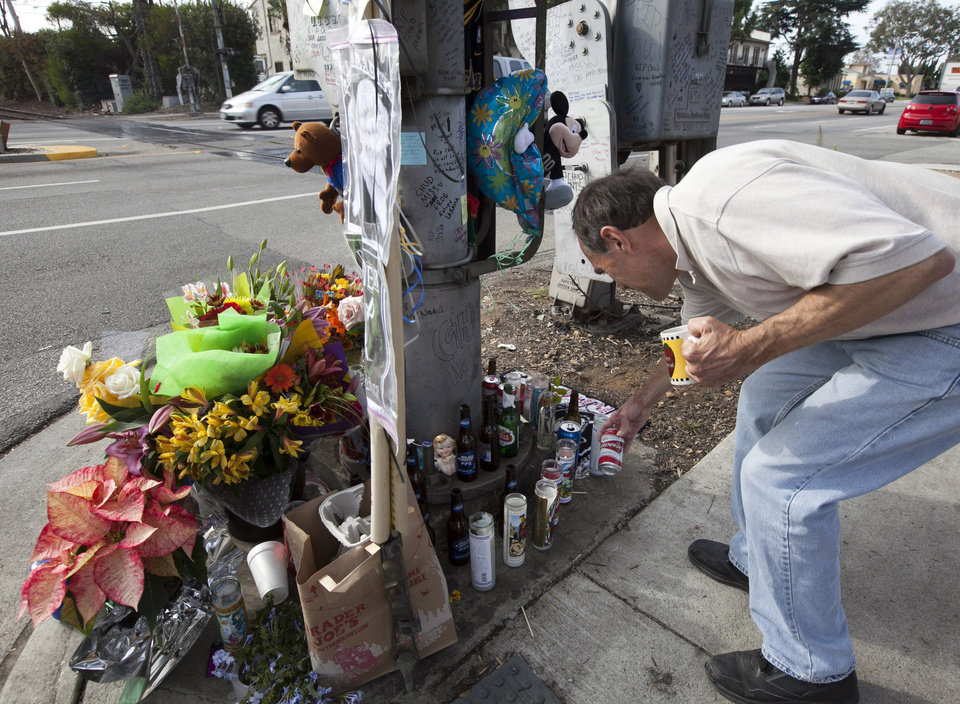 Photo -   Tim Swanson checking a memorial for victim, 31-year-old Phillip Moreno is shown in Torrance, Calif., Tuesday, Nov. 27, 2012. Moreno was struck late Saturday by a car driven by Sherri Wilkins. Los Angeles County prosecutors have filed murder and drunken-driving charges against Wilkins, a substance abuse counselor, who allegedly struck Moreno and drove for more than two miles with the dying victim on the hood of her car. Moreno died at a hospital. (AP Photo/Damian Dovarganes)