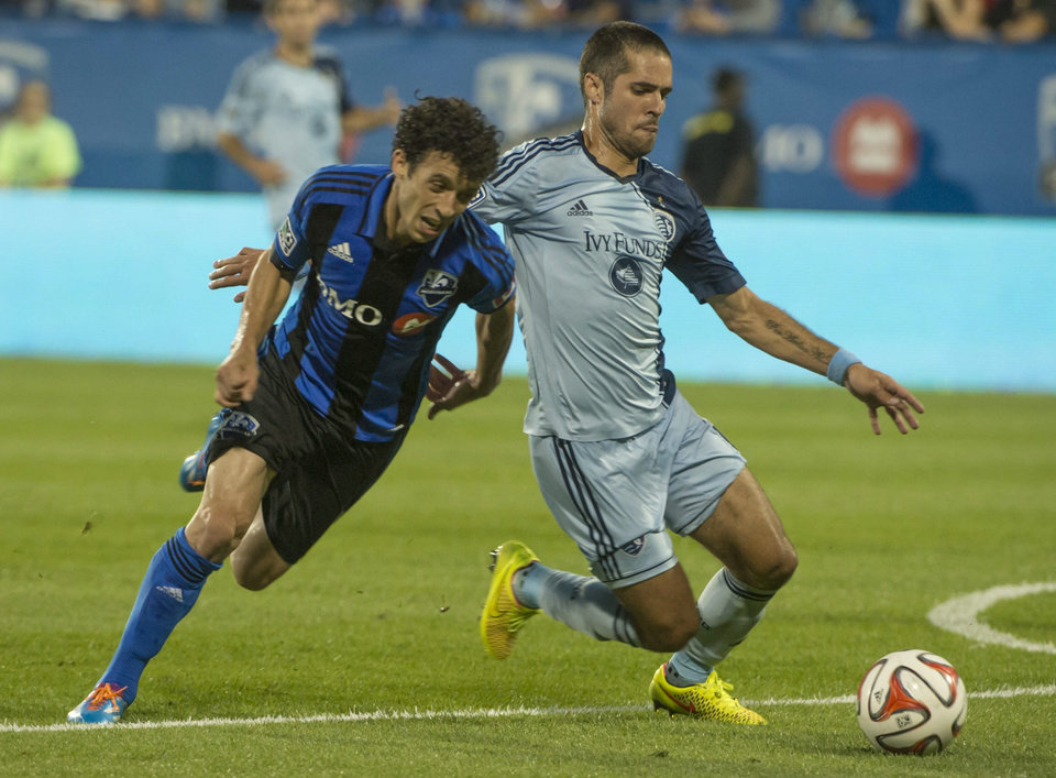 Photo - Montreal Impact's Felipe Martins and Sporting Kansas City's Benny Feilhaber battle for the ball during the second half of a soccer game, Saturday, July 12, 2014 in Montreal. (AP Photo/The Canadian Press, Peter McCabe)