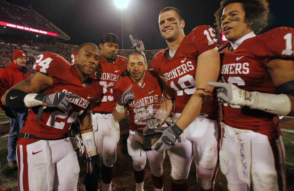 Photo - Oklahoma seniors Marcus Walker (24), Allen Patrick (23), Jacob Gutierrez (21), Joe Jon Finley (19) and Lewis Baker (16) celebrate with the Bedlam Trophy after the 49-17 win over Oklahoma State in the college football game between the University of Oklahoma Sooners (OU) and the Oklahoma State University Cowboys (OSU) at the Gaylord Family-Memorial Stadium on Saturday, Nov. 24, 2007, in Norman, Okla. 