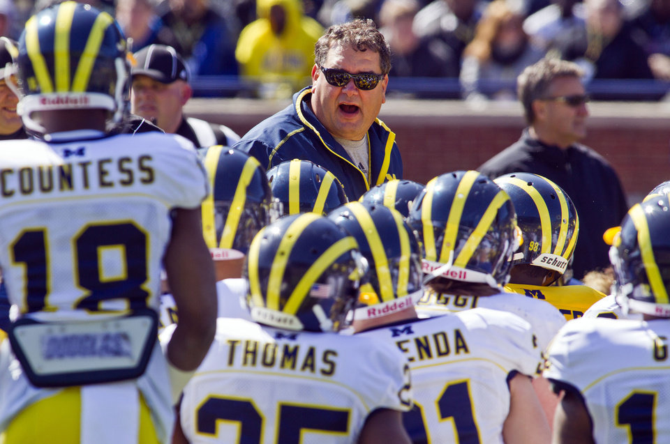 Photo - Michigan head coach Brady Hoke, center top, huddles with his players during the football team's NCAA college spring football game, Saturday, April 5, 2014, in Ann Arbor, Mich. (AP Photo/Tony Ding)