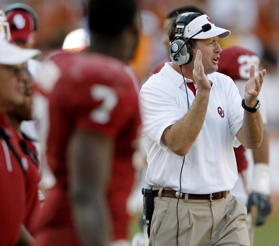 Photo - OU coach Bob Stoops applauds his team during the second half of the Red River Rivalry college football game between the University of Oklahoma Sooners (OU) and the University of Texas Longhorns (UT) at the Cotton Bowl on Saturday, Oct. 2, 2010, in Dallas, Texas.  OU defeated Texas 28-20.  Photo by Bryan Terry, The Oklahoman