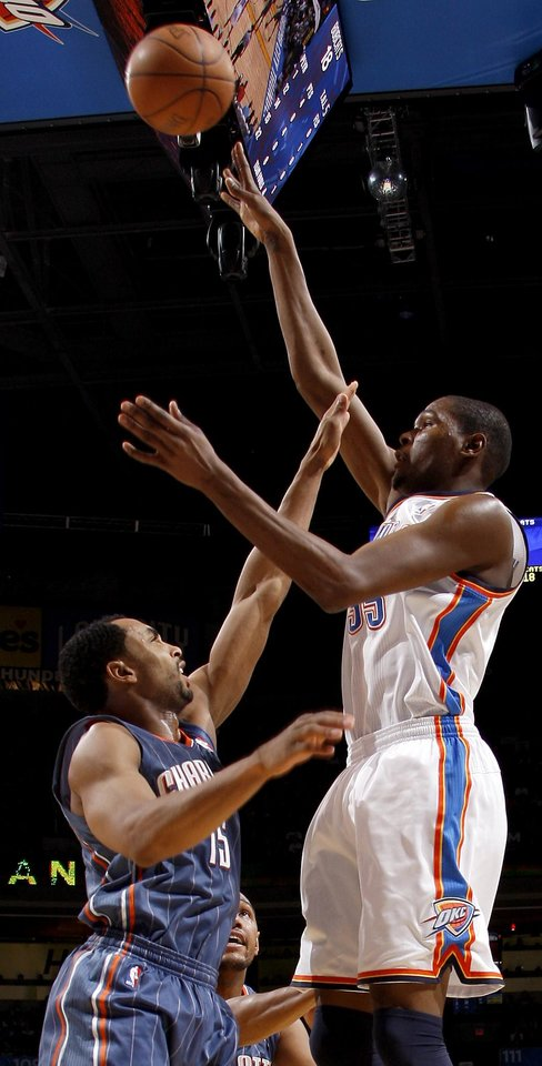 Oklahoma City's Kevin Durant (35) shoots the ball over Charlotte's Gerald Henderson (15) during an NBA basketball game between the Oklahoma City Thunder and the Charlotte Bobcats at the Oklahoma City Arena, Friday, March 18, 2011. Photo by Bryan Terry, The Oklahoman