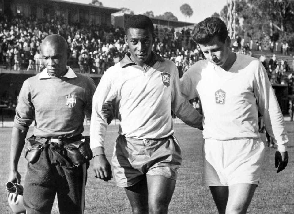 Photo - FILE - In this Feb. 1962, file photo, shows Edson Arantes do Nascimento known as Pele, center, trainer Mario Americo, left, and Czech player Masopust.  After Neymar's injury in this 2014 Soccer World Cup while playing against Colombia, Brazil remembers when Pele, its best player in the Chile 1966 World Cup was also sidelined because of injury in the tournament, and Brazil still won the title. (AP Photo, File)