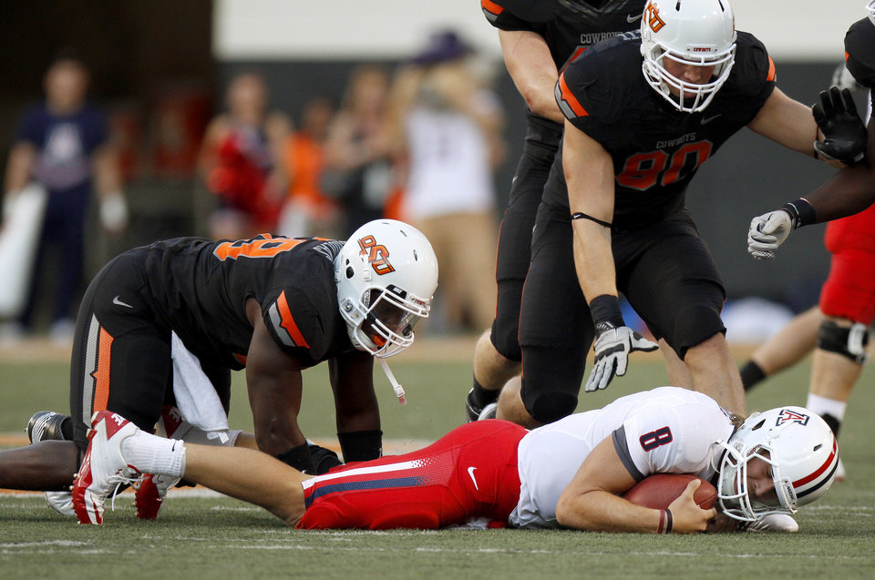 Photo - Oklahoma State's Nigel Nicholas (89) and Cooper Bassett (80) stand over Arizona's Nick Foles (8) after a sack during their game Thursday in Stillwater. PHOTO BY BRYAN TERRY, The Oklahoman
