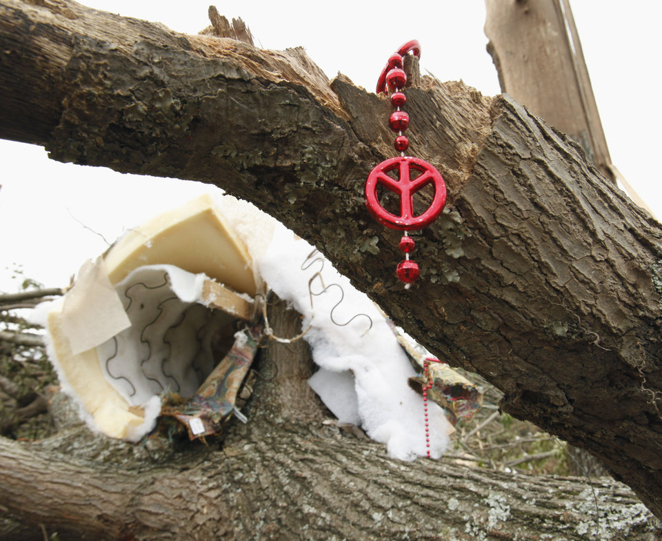 Photo - Beads and a mattress hang from a tree on the hillside north of Highway 9 near SE 192 on Wednesday, May 12, 2010, in Norman, Okla.   A mother died and her children were injured  at this location during Monday's severe storms.  Photo by Steve Sisney, The Oklahoman