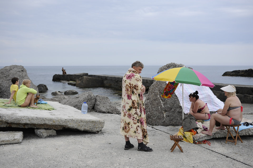 Photo - Russian tourists enjoy a visit to a  Black Sea beach about 35 kms (22 miles) from Yalta, Crimea, Sunday, June 15, 2014. When Russia annexed the Black Sea peninsula of Crimea earlier this year, it regained not only harbors for its navy and abandoned Ukrainian military bases but also long stretches of pebble beaches that were the summer destination of choice for millions of Soviet citizens. The Kremlin is hoping to attract tourists to Crimea, which Russia annexed in March, by asking state-controlled companies to send their employees on free vacation trips.(AP Photo/Andrew Lubimov)