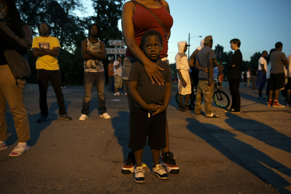 Photo - Jeremiah Parker, 4, stands in front of his mother, Shatara Parker, as they attend a protest Wednesday, Aug. 13, 2014, in Ferguson, Mo. Nights of unrest have vied with calls for calm in a St. Louis suburb where Michael Brown, an unarmed black teenager was killed by police, while the community is still pressing for answers about the weekend shooting. (AP Photo/Jeff Roberson)