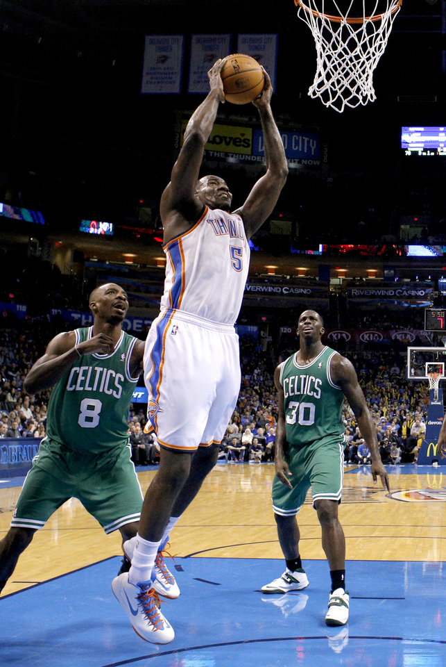 Photo - Oklahoma City's Kendrick Perkins (5) goes up for a basket as Boston's Jeff Green (8) and Brandon Bass (30) look on during the NBA game between the Oklahoma City Thunder and the Boston Celtics at the Chesapeake Energy Arena., Sunday, Jan. 5, 2014. Photo by Sarah Phipps, The Oklahoman