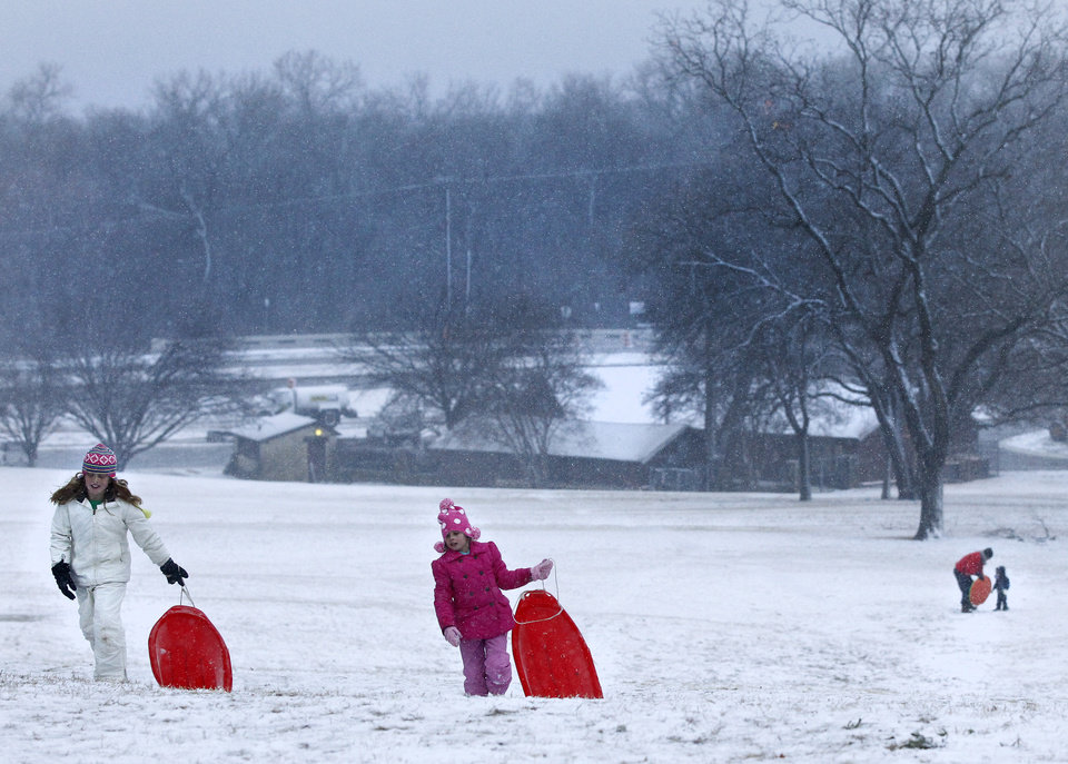 Photo - Lauren Parnell, 9, left, and Ella Sweeney, 6, climb to the top of the hill for another sled run at Flag Pole Hill Park in Dallas, on Tuesday, Dec. 25, 2012. (AP Photo/The Dallas Morning News, Stan Olszewski)  MANDATORY CREDIT; MAGS OUT; TV OUT; INTERNET OUT; AP MEMBERS ONLY