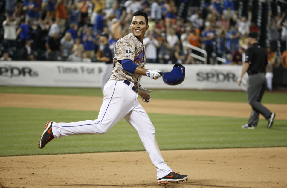 Photo - New York Mets Ruben Tejada (11) smiles as he looks back at his teammates after hitting an 11th inning, game-winning, walk-off, RBI single in the Mets 4-3 victory over the Atlanta Braves in a baseball game in New York, Monday, July 7, 2014. (AP Photo/Kathy Willens)