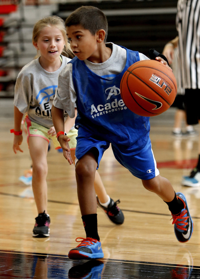Photo - Jacob Davis, 8, goes around Makala Johnson, 7, during Kevin Durant's basketball camp on Thursday, Aug. 7, 2014 in Moore, Okla. Photo by Steve Sisney, The Oklahoman