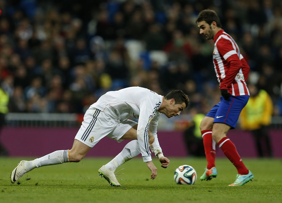 Photo - Real's Cristiano Ronaldo, left falls during a semi final, 1st leg, Copa del Rey soccer derby match between Real Madrid and Atletico Madrid at the Santiago Bernabeu Stadium in Madrid, Wednesday Feb. 5, 2014.  (AP Photo/Paul White)