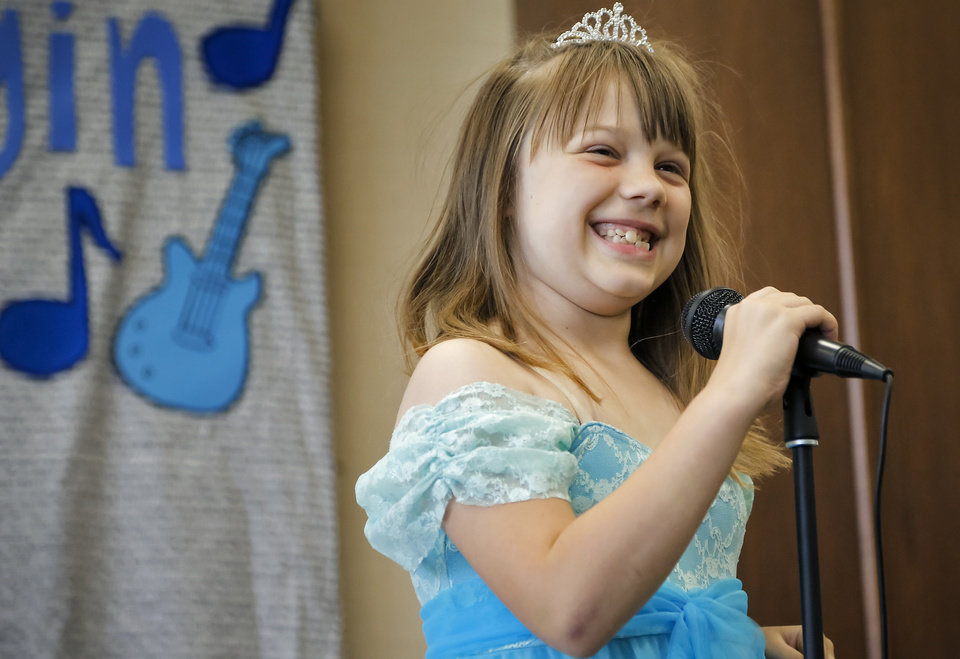 Photo - Ashlyn Burke smiles after performing her song during the  Camp Noggin  talent show  at Youth and Family Services in El Reno, Okla. on Thursday, June 5, 2014. The camp that is held for children with autism to have a place to take part in summer activities .  Photo by Chris Landsberger, The Oklahoman   CHRIS LANDSBERGER - CHRIS LANDSBERGER