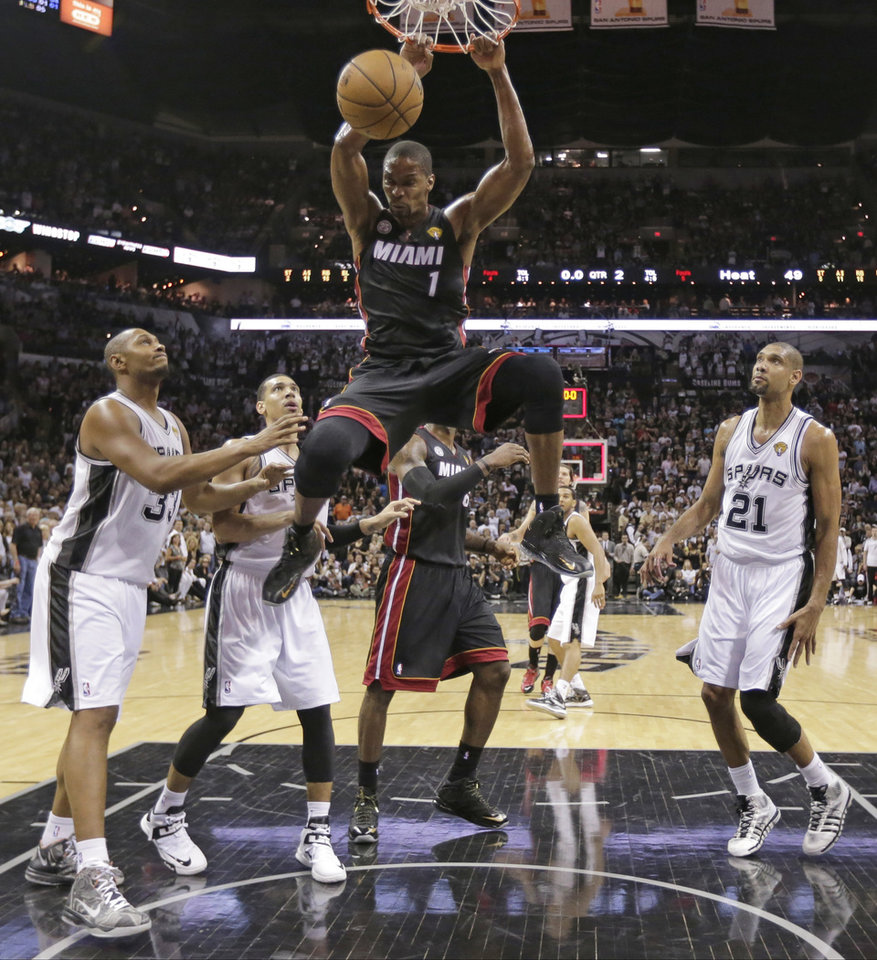 Photo - Miami Heat's Chris Bosh (1) dunks against the San Antonio Spurs during the first half at Game 4 of the NBA Finals basketball series, Thursday, June 13, 2013, in San Antonio. (AP Photo/Eric Gay)