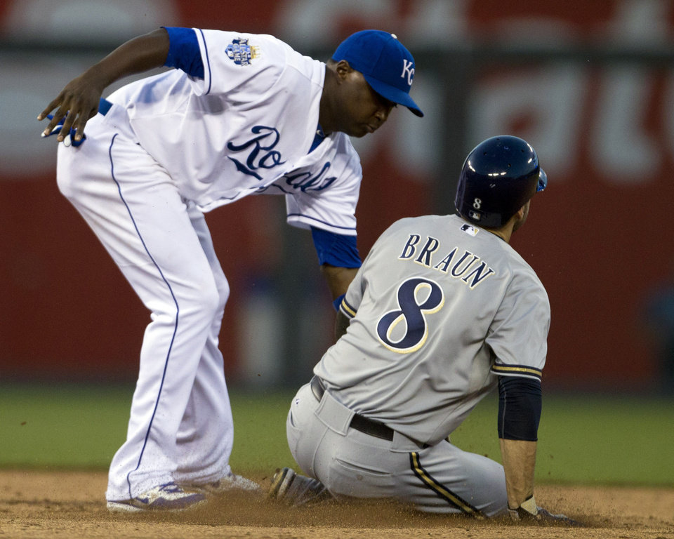 Photo -   Kansas City Royals shortstop Yuniesky Betancourt, left, tags out Milwaukee Brewers' Ryan Braun (8) during the fifth inning of a baseball game at Kauffman Stadium in Kansas City, Mo., Wednesday, June 13, 2012. Braun was caught stealing on the play. (AP Photo/Orlin Wagner)