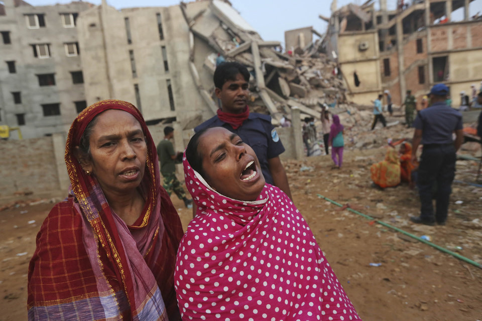 Bangladeshi relatives of missing workers wait at the site of a building that collapsed Wednesday in Savar, near Dhaka, Bangladesh, Friday, April 26, 2013. The death toll reached hundreds of people as rescuers continued to search for injured and missing, after a huge section of an eight-story building that housed several garment factories splintered into a pile of concrete.(AP Photo/Kevin Frayer)