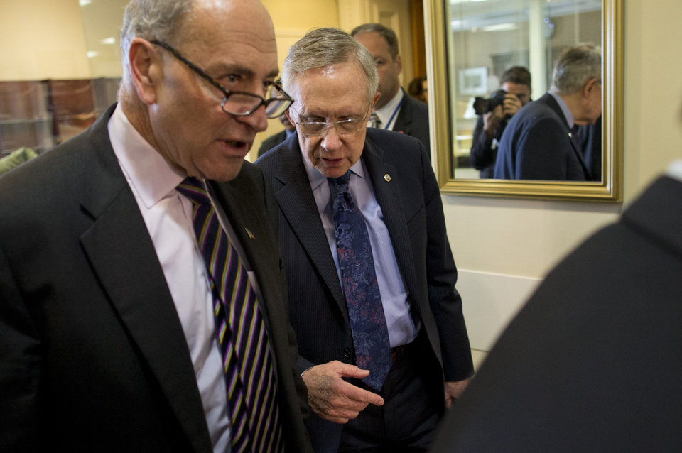 Photo - Sen. Chuck Schumer, D-N.Y., left, and Senate Majority Leader Sen. Harry Reid, D-Nev., arrive for a news conference on Capitol Hill on Saturday, Oct. 12, 2013 in Washington. The federal government remains partially shut down and faces a first-ever default between Oct. 17 and the end of the month. (AP Photo/ Evan Vucci)