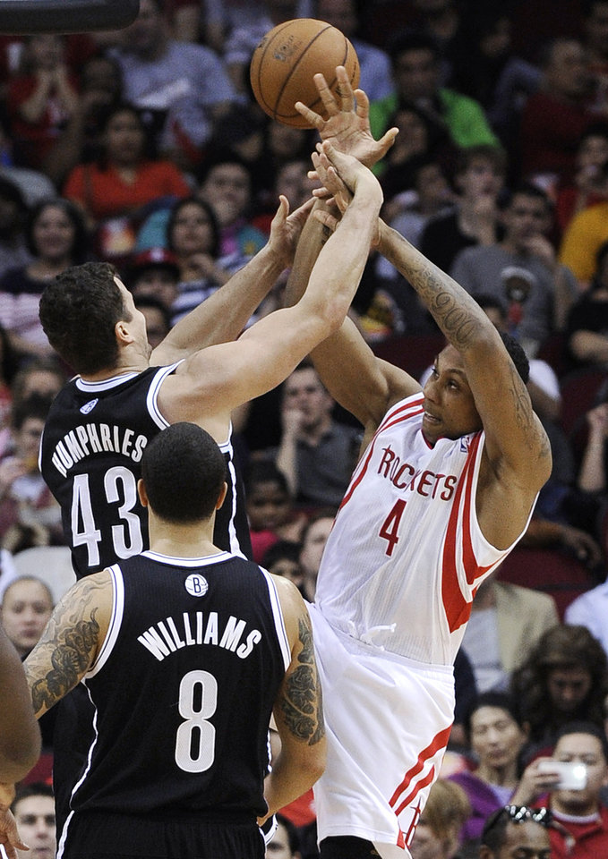 Photo - Houston Rockets' Greg Smith (4) is fouled by Brooklyn Nets' Kris Humphries (43) as Deron Williams (8) watches during the first half of an NBA basketball game Saturday, Jan. 26, 2013, in Houston. (AP Photo/Pat Sullivan)