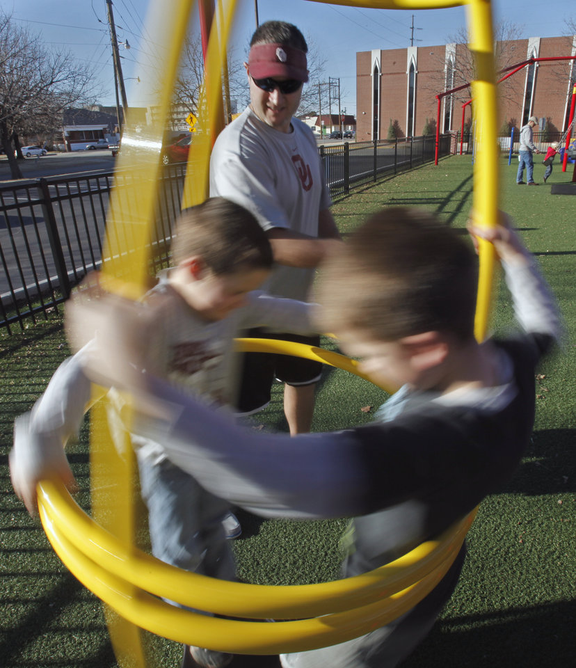 Ryan Redwine spins sons Holdan 5, (Left) and Tillman, 6, as the family enjoys the warm weather at a playground at First Baptist Church on Wednesday, Dec. 28, 2011, in Norman, Okla.  Redwine, from Marietta, is visiting family in Norman over the holidays.  Photo by Steve Sisney, The Oklahoman
