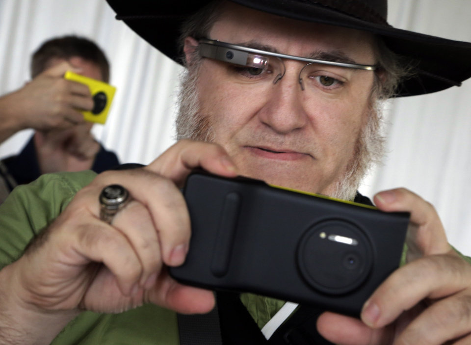 Photo - Journalist Andy Inahtko, from Chicago, wearing Google Glass, tests a Nokia Lumia 1020 at its introduction,  in New York,  Thursday, July 11, 2013. The Nokia Lumia 1020, with a 41-megapixel camera, records more detail than other camera phones and even tops point-and-shoot cameras. (AP Photo/Richard Drew)