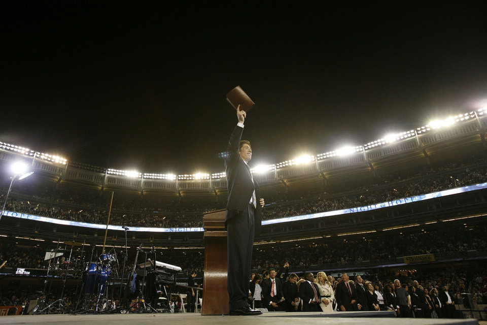 Evangelist Joel Osteen lifts his Bible during one of his �A Night of Hope� events. The Houston preacher and author will present �A Night of Hope� Sept. 28 at the Chesapeake Energy Arena in downtown Oklahoma City.  Photo provided