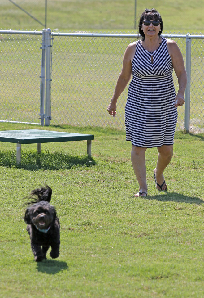 Photo -  Coco McBurney and her dog Sadie, of Upland, Calif., take a break from traveling Wednesday at the OnCue dog park. [Photo By Steve Gooch, The Oklahoman]