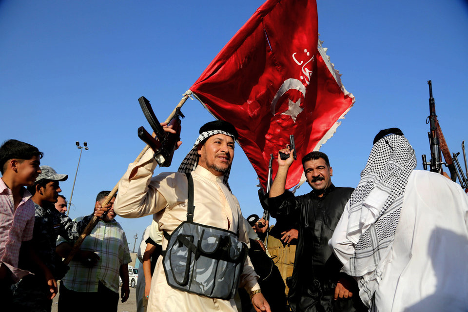 Photo - In this Tuesday, June 17, 2014 photo, Iraqi Shiite tribal fighters raise their weapons and chant slogans against the al-Qaida-inspired Islamic State of Iraq and the Levant, after authorities urged Iraqis to help battle insurgents, in Baghdad's Sadr city, Iraq. Thousands of Shiites from Baghdad and across southern Iraq answered an urgent call to arms Saturday, joining security forces to fight the Islamic militants who have captured large swaths of territory north of the capital and now imperil a city with a much-revered religious shrine. (AP Photo/Karim Kadim)