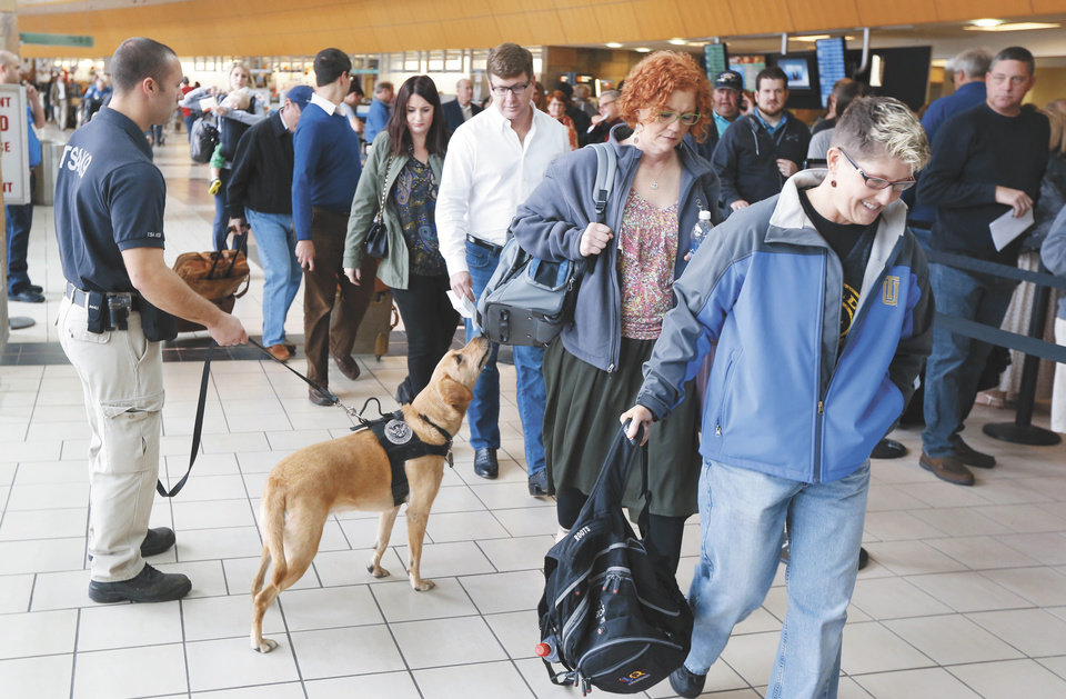 A TSA K-9 officer checks passengers' carry-on luggage at Will Rogers World Airport in Oklahoma City. A new pre-screening program allows certain travelers to go through security without removing shoes, jackets and laptops. <strong>Steve Gooch - The Oklahoman</strong>