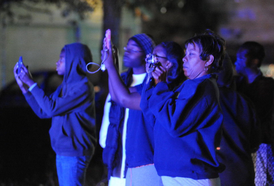 Photo -   The flashing blue lights of nearby police cars light onlookers trying to capture the scene where authorities say a small plane carrying three people crashed into a home in Jackson, Miss. shortly after 5 p.m. Tuesday evening, Nov. 13, 2012. (AP Photo/The Clarion-Ledger, Joe Ellis) NO SALES